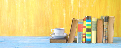 Old books in a row and a cup of coffee Royalty Free Stock Photo