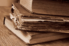 Old books on a rustic wooden table, sepia toning Royalty Free Stock Photos
