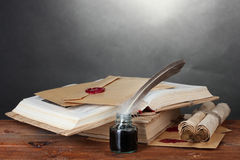 Old books, scrolls, feather pen and inkwell. On wooden table on grey background Royalty Free Stock Photos