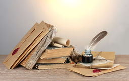 Old books, scrolls, feather pen and inkwell. On wooden table on grey background Royalty Free Stock Images