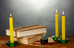 Old books, scrolls, ink pen inkwell and candles Stock Images