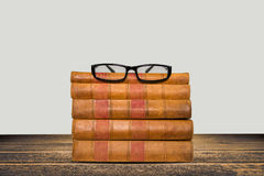 Old books shelf isolated on wooden table Stock Photos