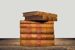 Old books shelf isolated on wooden table Stock Images