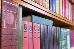 Old books on a shelf perspective. Old retro  books  with color covers on a shelf  perspective background.Hard strong selective focus. Mass production Royalty Free Stock Photos