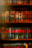 Old books on the shelves. Old books in library archives sunlit with golden rays Royalty Free Stock Photos
