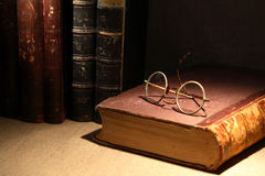 Old Books And Spectacles. Vintage still life with old books and spectacles on canvas surface Stock Image