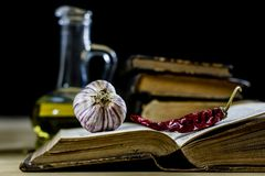 Old books and spices. Dried peppers and recipes. Old kitchen table. Black background royalty free stock images