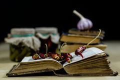 Old books and spices. Dried peppers and recipes. Old kitchen table. Stock Photography