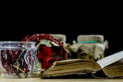 Old books and spices. Dried peppers and recipes. Old kitchen table. Black background royalty free stock photos