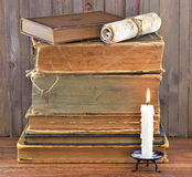 Old books in spider web with candle. Old shabby books with candle on wooden background Royalty Free Stock Photos