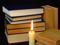 Old books stacked in a pile and a burning candle. royalty free stock images