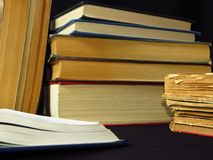 Old books stacked in a pile. Education, knowledge, reading habits, paper. Closeup of books pile. A pile of old books is pictured against dark black background stock photo