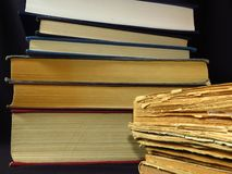Old books stacked in a pile. Education, knowledge, reading habits, paper, library. Closeup of books pile. A pile of old books is pictured against dark black stock photos