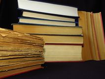 Old books stacked in a pile. Education, knowledge, reading habits, paper, library. Closeup of books pile. A pile of old books is pictured against dark black royalty free stock photography