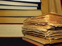 Old books stacked in a pile. Education, knowledge, reading habits, paper, library. Closeup of books pile. A pile of old books is pictured against dark black stock image