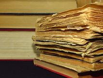 Old books stacked in a pile. Education, knowledge, reading habits, paper, library, mystery. Closeup of books pile. A pile of old books is pictured against dark royalty free stock photography
