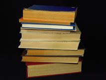 Old books stacked in a pile. Education, knowledge, reading habits, paper, library. Closeup of books pile. A pile of old books is pictured against dark black royalty free stock photo