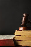 Old Books Stacked and Topped with Wooden Gavel - Chalkboard Back. Eye level law concept shot of old books stacked and topped with wooden gavel. Open book to left Stock Images