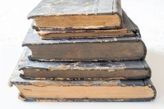 Old books stacked on a white table. Old release without titles. White background Royalty Free Stock Image