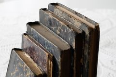 Old books stacked on a white table. Old release without titles. White background Stock Photos