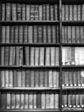 Old books stacked on wooden shelves. Old reference books stacked on wooden shelves Royalty Free Stock Photo