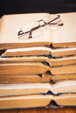 Old books in studio. Some open old books with glasses in studio Stock Photos