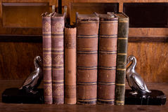 Old books with supports. Old books on wooden table with antique metallic gooses supports Stock Photography