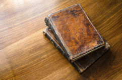 Old books on a table. Old books with brown leather covers on a wooden surface Stock Photo