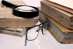 Old books on a table. Old books with glasses lay on a table Royalty Free Stock Photography