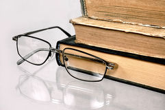 Old books on a table. Old books with glasses lay on a table Stock Photography