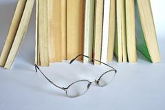 Read an old book at home. Old books on the table, an open book and reading glasses. Part of a series Royalty Free Stock Photo