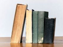 Old books on table. A stack of old books on a wooden table in a level set one stock photography