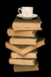 Old Books and Teacup. An antique teacup sitting on a stack of old books, isolated against black stock photography