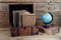 Old books in vintage chest closeup on wooden table Royalty Free Stock Images