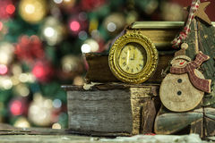 Old books and vintage clock on Christmas background. New year card in retro style Royalty Free Stock Photos