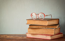 Old books with vintage glasses on a wooden table. retro filtered image Royalty Free Stock Images