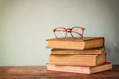 Old books with vintage glasses on a wooden table. retro filtered image. Royalty Free Stock Images
