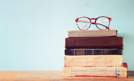 Old books with vintage glasses on a wooden table. retro filtered image Royalty Free Stock Photography