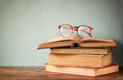 Old books with vintage glasses on a wooden table. retro filtered image Stock Photo