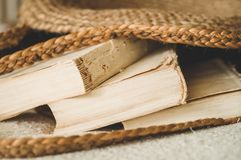 Old books and vintage straw bag on white warm blanket. Bag straw summer woman. Brown handmade nature bag royalty free stock images