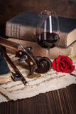 Old books, violin scroll and red rose. On wooden background Stock Image