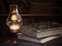 Old books on a wooden table, antique lamp Stock Photography