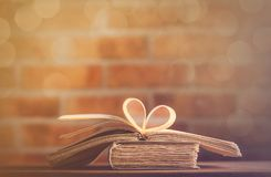 Old books on wooden table at fairy lights background. Library Royalty Free Stock Photography
