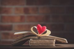 Old books on wooden table at fairy lights background. Library Stock Photo
