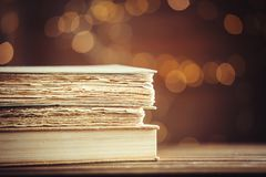 Old books on wooden table at fairy lights background. Library Royalty Free Stock Photos