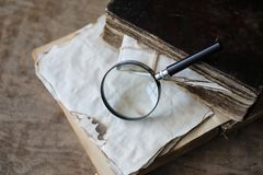 Old books on a wooden table and magnifier Royalty Free Stock Photos