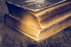 Old books on wooden table in a grunge style. Royalty Free Stock Photo