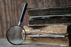 Old books on a wooden table and magnifier Stock Photography