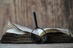 Old books on a wooden table and magnifier Stock Photos