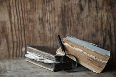 Old books on a wooden table and magnifier Stock Images